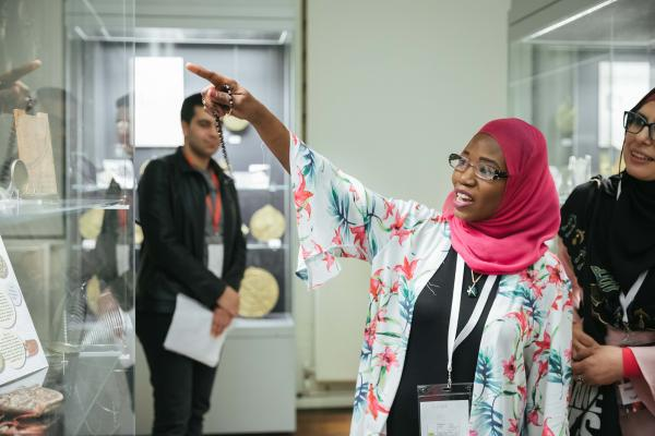 Muslim woman wearing pink hijab (Islamic headscarf) giving a tour of the Museum, she is pointing to an astrolabe in a case.